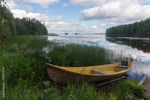 Fototapety, obrazy: Yellow wooden boat on the shore of a picturesque lake