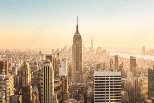 Photo Stands New York New York City. Manhattan downtown skyline with illuminated Empire State Building and skyscrapers at amazing golden sunset. USA.