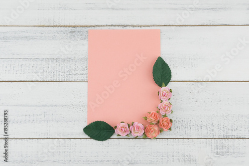 c39208f038c Blank pink card decorate with pink rose paper flowers and green leaves on  white wood background