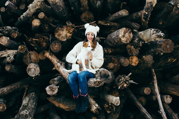 .Sweet and pretty girl sitting on a wooden log playing with her nice dog jack russell outdoors in the mountain on a sunny winter day. Lifestyle.