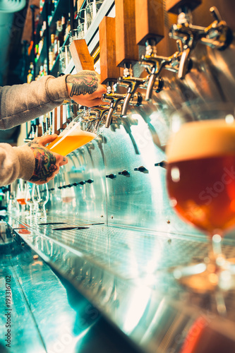 Foto op Aluminium Alcohol Hand of bartender pouring a large lager beer in tap.