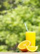 Tall glass of tasty freshly squeezed orange juice standing on an outdoor wooden table on a hot summer day with slices of orange