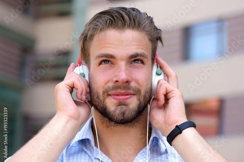 Láminas  Man with unshaven face enjoy sound with modern headphones.