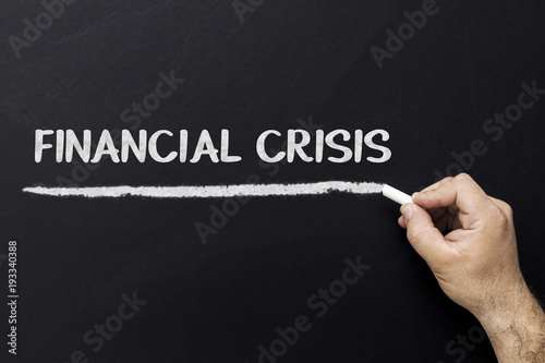 Photo  Hand writing Financial crisis on a chalkboard