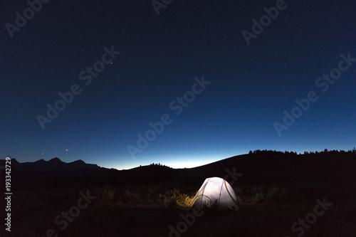 Illuminated tent under starry sky at night, Sawtooth Wilderness foothills, Stanley, Idaho, USA