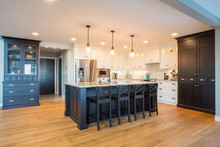 Custom Kitchen With Built In Appliances, Hard Wood Floors, And Light And Dark Cabinetry