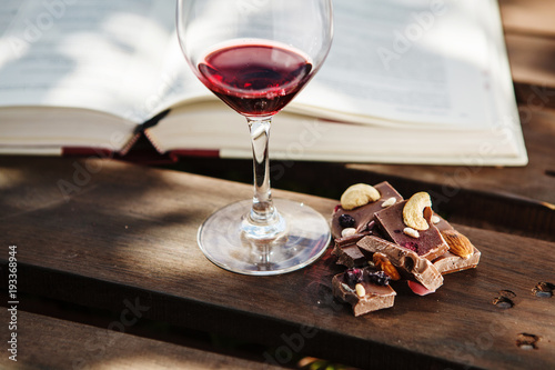 Vin Glass with wine and pieces of chocolate near open book