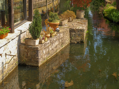 City on the water River L´Eure with flowerpots and bushes in the old town of Chartres in France
