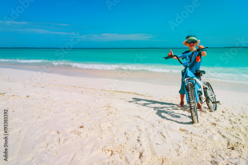 Foto op Plexiglas little boy riding bike on tropical beach
