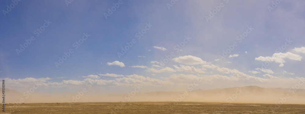 Panoramic view of sand storm blowing across the Mojave Desert in southern California wilderness.