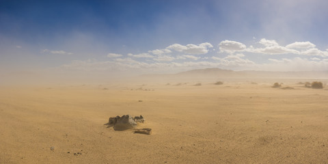 Stone ring forms a fire pit in a vast sand desert under the cloud of a growing sandstorm.