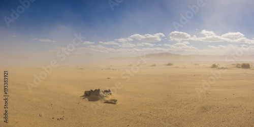 Poster Zandwoestijn Stone ring forms a fire pit in a vast sand desert under the cloud of a growing sandstorm.
