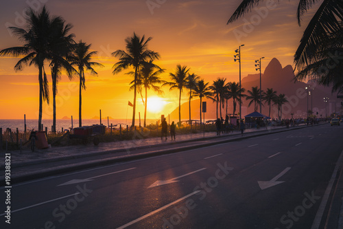 Sunset over Ipanema Beach with Dois Irmaos mountains in Rio de Janeiro, Brazil. People walking by the beach.