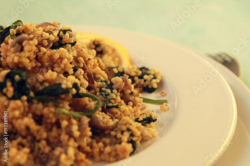 Millet with mushrooms and spinach. Close up. Vegan dish. Vegetarian couscous on the round white plate.