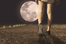 A Women And Sneaker Shoes Walking Under Full Moon At Night