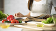 Leinwandbild Motiv Housewife reading cooking book with fresh vegetables and kitchen tools on table