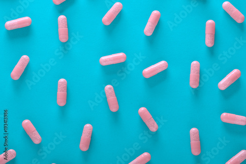 Fotografia  pink pills on blue background top view
