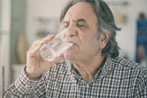 Canvas Print Senior man drinking water from glass in kitchen