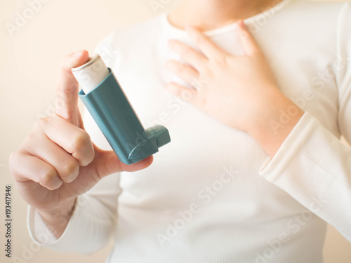 Fotografie, Obraz Young female in white t-shirt using blue asthma inhaler for relief asthma attack