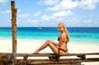 Woman sitting on the Zanzibar's white sand beach