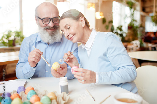 Photo  Aged couple with eggs and paintbrushes sitting by table and sharing creative ide