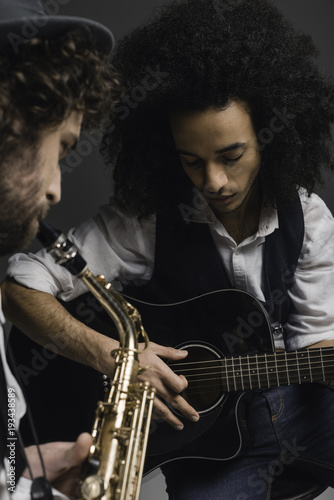 Staande foto Muziekband young duet of musicians playing sax and acoustic guitar on black