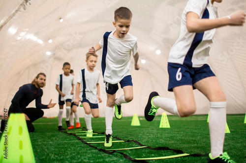 Row of boys running on green football field during training with instructor