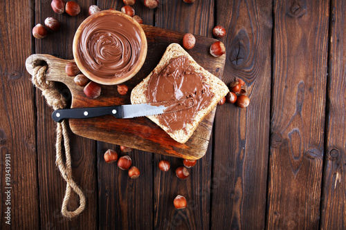 Valokuva  Homemade hazelnut spread with toast and in wooden bowl for breakfast