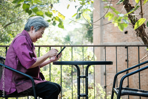 elder woman holding mobile phone on terrace Poster