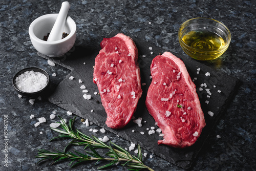 Two raw picanha steaks on a cutting board with spices on a dark background Canvas Print
