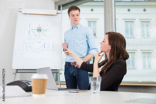 Fototapety, obrazy: Businessman Looking At Female Coworker Pointing On Chart