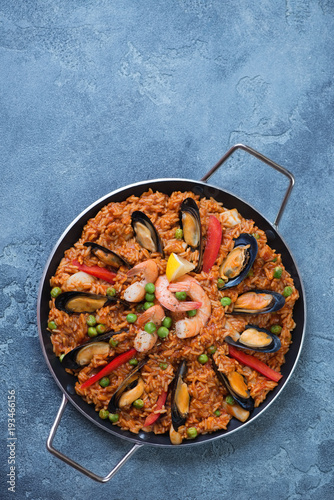 Frying pan with seafood paella on a blue stone background, vertical shot with space, above view
