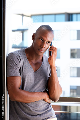 Fotografie, Obraz  handsome african american man leaning against wall and talking on cellphone
