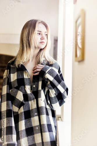 Fotografia  girl in a shirt by the window sill
