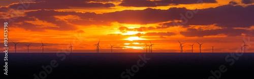 Zdjęcie XXL Panoramiczny zachód słońca z turbin wiatrowych w morskiej farmy wiatrowej. Wiele turbin wiatrowych w morzu i chmury na niebie. Energia elektryczna, która jest zrównoważona, alternatywna, odnawialna, ekologiczna i zapobiega zmianom klimatycznym