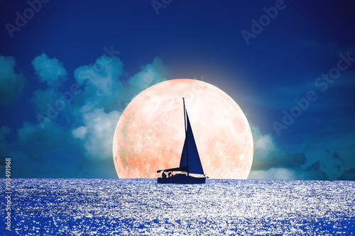 Silhouette of a boat with full Moon on the ocean.