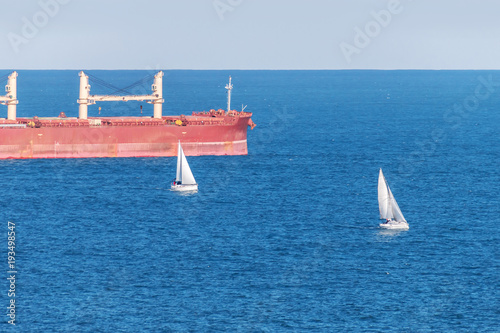 Fotografía  Peaceful marine landscape showing red freighter and small white sail boats over