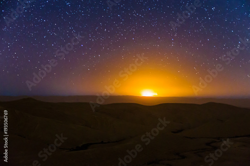 Foto op Aluminium Diepbruine Night sky stars over desert hills sunset light.