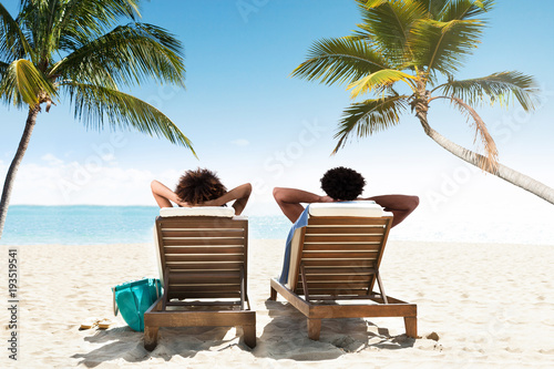 Valokuva Couple relaxing on deck chairs at beach resort