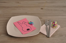 An Easter Place Setting With A Napkin, Plate, Knife, Fork And A Bowl Of Candy Displayed On A Table With An Easter Bunny Card