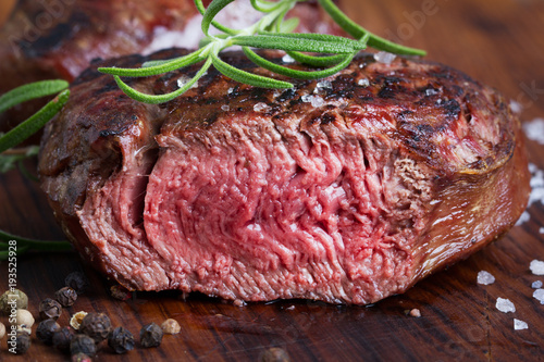 Papiers peints Steakhouse grilled cut beef steak with rosemary and seasoning on wooden board