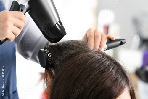 Professional hairdresser drying client's hair in beauty salon Wallpaper Mural
