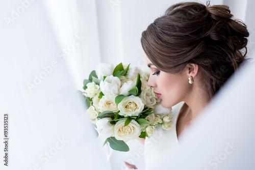 Fotografia attractive brunette bride sniffing wedding bouquet