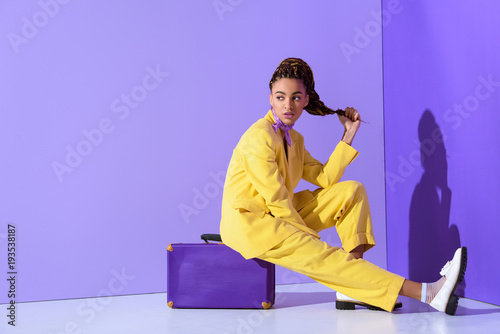 Obraz african american girl posing in yellow suit sitting on purple suitcase, on trendy ultra violet background - fototapety do salonu