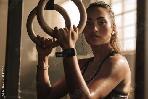 Determined woman exercising with gymnastic rings