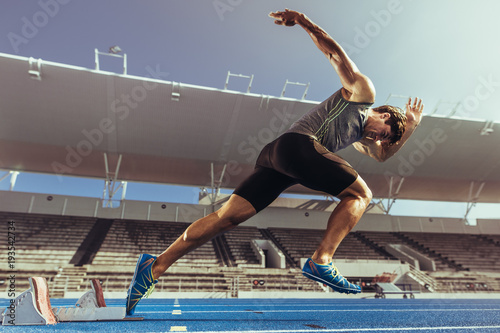 Obraz na płótnie Sprinter taking off from starting block on running track