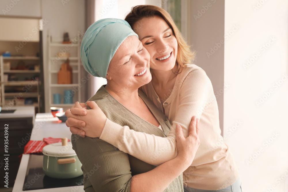 Fototapeta Young woman visiting her mother with cancer indoors