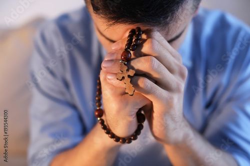 Fotomural Religious young man with rosary beads praying at home, closeup