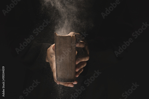 Fototapeta Priest with old Bible on black background, closeup