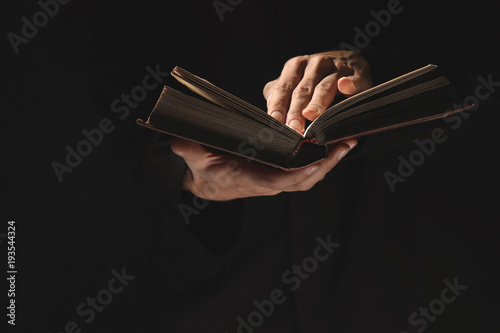 Obraz na plátně  Priest with old Bible on black background, closeup